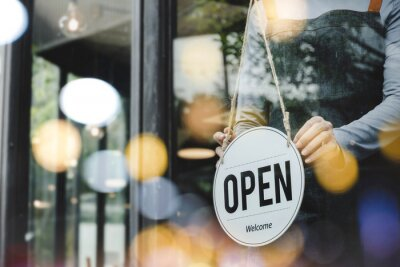 Fototapeta hand of asain staff woman wearing apron turning open sign board on glass door in modern cafe coffee shop, hotel service, cafe restaurant, retail store, small business owner, food and drink concept