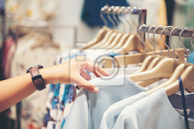 Fototapeta hand of customer choosing clothes in a clothing store
