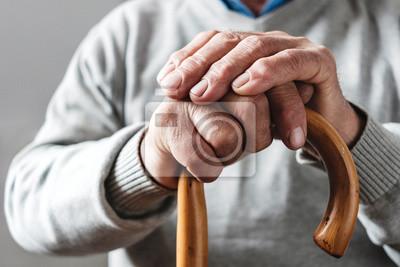 Fototapeta Hands of an elderly man resting on a walking cane