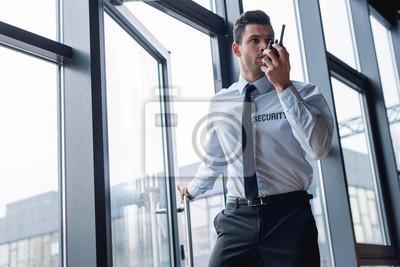 Fototapeta handsome guard in suit talking on walkie-talkie