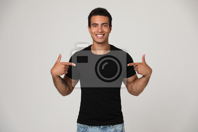 Fototapeta Handsome young African-American man in blank t-shirt on light background. Space for design