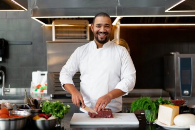 Fototapeta Handsome young African chef standing in professional kitchen in restaurant preparing a meal of meat and cheese vegetables.