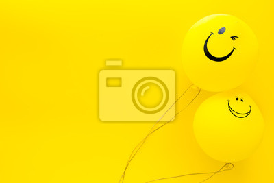 Fototapeta Happiness emotion. Yellow balloon with smile on yellow background top view space for text
