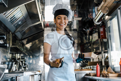 Fototapeta happy asian chef holding carton plates in food truck