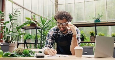 Fototapeta Happy Caucasian businessman talking on cellphone while standing in apron in small floral center and writing down order details. Joyful male florist calling on smartphone at work. Own business concept