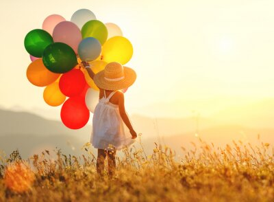 Fototapeta . happy child with balloons at sunset in summer
