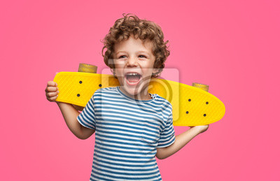 Fototapeta Happy curly boy laughing and holding skateboard