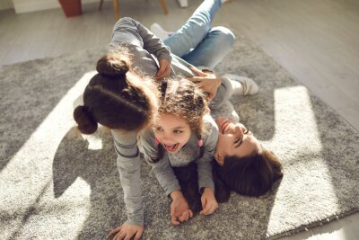 Fototapeta Happy family enjoying quality time at home. Mom and little children frolicking on carpet. Cheerful mother and funny carefree kids playing, laughing and having fun on floor rug in sunny living-room