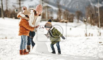 Fototapeta happy family mother and children having fun on winter walk