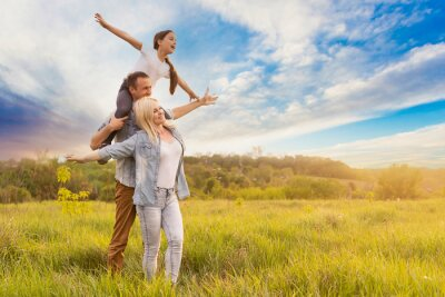 Fototapeta Happy family: mother father and child daughter on nature on sunset