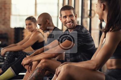 Fototapeta Happy fitness class resting in conversation