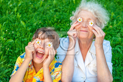 Fototapeta Happy grandmother and laughing   grandchild fooling around the law of putting chamomiles instead of eyes. Family love and relationships. Family happy holiday.