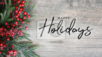 Fototapeta Happy Holidays Text with Holiday Evergreen Branches and Berries Over Rustic Wooden Background
