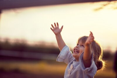 Fototapeta Happy kid looking at the sky . fun on countryside, sunset golden hour. Freedom nature concept.