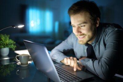 Fototapeta Happy man using laptop in the night at home