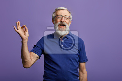Fototapeta happy positive handsome old man shows Ok sign, no problems, health is ok.everything is ok. close up portrait. isolated blue background. happiness, success concept
