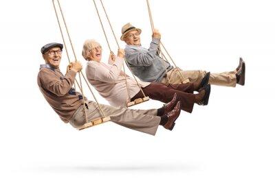 Fototapeta Happy senior people swinging on swings