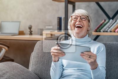 Fototapeta Happy senior woman looking and laughing at her digital tablet on sofa