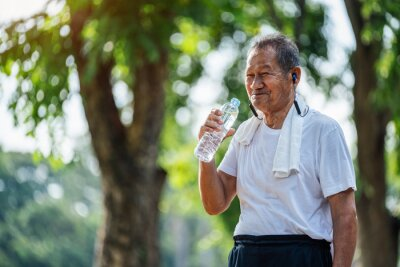 Fototapeta Happy thirsty senior man drinking fresh water after sports in park, Concept of senior healthy lifestyle.