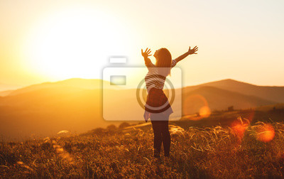 Fototapeta Happy woman jumping and enjoying life  at sunset in mountains.
