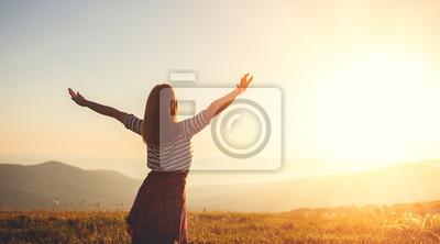 Fototapeta Happy woman jumping and enjoying life  at sunset in mountains