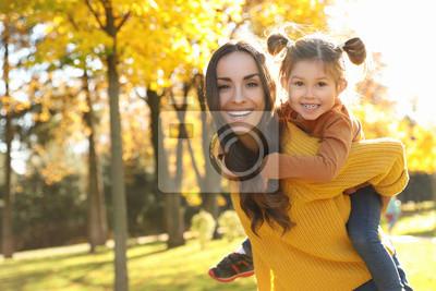 Fototapeta Happy woman with little daughter in sunny park. Autumn walk