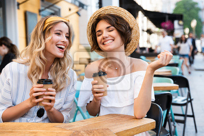 Fototapeta Happy young positive optimistic girls friends sitting outdoors in cafe drinking coffee talking with each other.