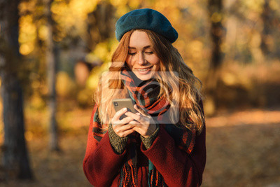 Fototapeta Happy young pretty woman walking outdoors in autumn spring park using mobile phone chatting.