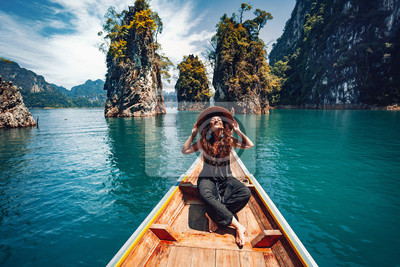 Fototapeta happy young woman tourist in asian hat on the boat at lake