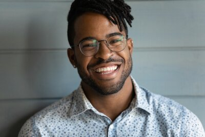 Fototapeta Head shot of happy handsome African American guy with trendy haircut and dreads, black stubble, stylish glasses, looking at camera with toothy smile. Millennial young man, student close up portrait