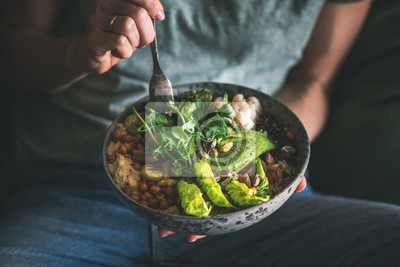 Fototapeta Healthy dinner or lunch. Woman in t-shirt and jeans eating vegan superbowl or Buddha bowl with hummus, vegetable, salad, beans, couscous and avocado