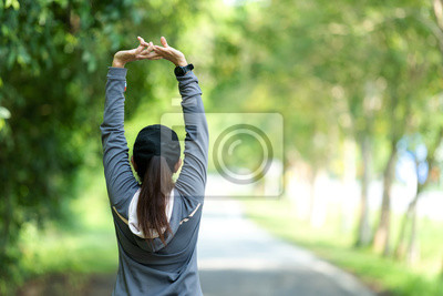 Fototapeta Healthy woman warming up stretching her arms. Asian runner woman workout before fitness and jogging session on the road nature park. Healthy and Lifestyle Concept