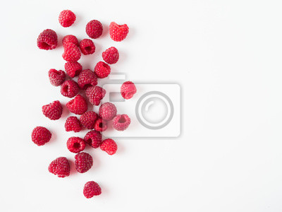 Fototapeta Heap of fresh ripe red raspberries on white background. Raspberry with copy space for text or design. Top view or flat lay.