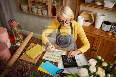 Fototapeta High angle portrait of female businesswoman counting finances using calculator in small shop, copy space