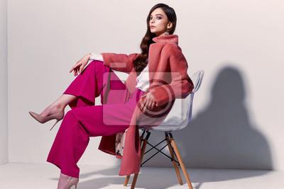 Fototapeta High fashion portrait of young elegant woman. Coral coat, magenta pants, white blouse.