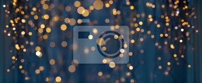 Fototapeta holiday illumination and decoration concept - christmas garland bokeh lights over dark blue background