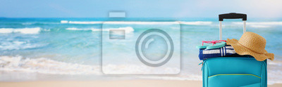 Fototapeta holidays. travel concept. blue suitcase with female hat, flipflops in front of tropical marina background