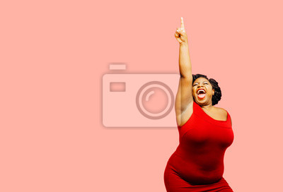 Fototapeta Horizontal portrait of a very happy and excited woman celebrating success with arm up, mouth open and finger pointing up
