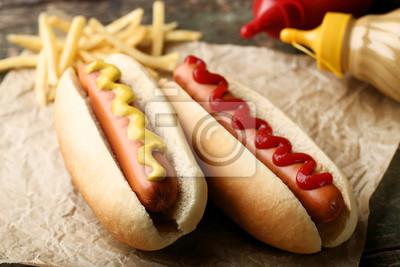 Fototapeta Hot dog z musztardą i ketchupem na drewnianym stole