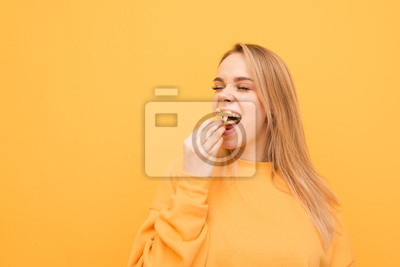 Fototapeta Hungry attractive girl eats a lot of French fries, holds a handful of snacks and puts it in the mouth. Close-up portrait of a girl greedily eats French fries on a yellow background