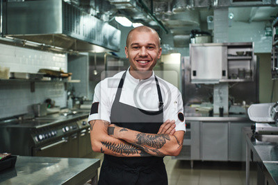 Fototapeta I love my work Cheerful young chef in apron keeping tattooed arms crossed and smiling while standing in a restaurant kitchen