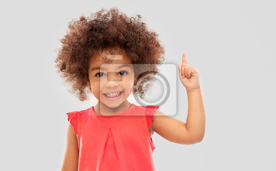 Fototapeta idea, warning and childhood concept - happy little african american girl pointing finger up over grey background