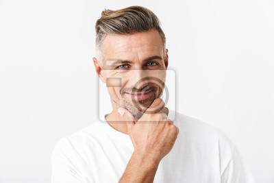 Fototapeta Image of optimistic man 30s with bristle wearing casual t-shirt smiling and touching chin