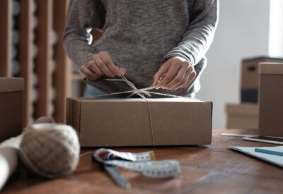 Fototapeta Indian mixed-race female business owner working, packing the order for shipping to customer