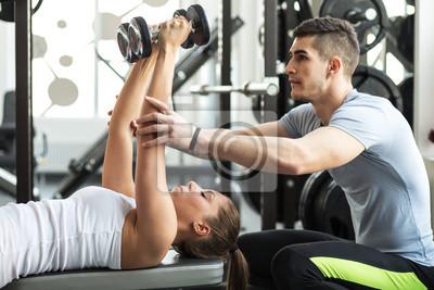 Fototapeta Instruktor fitness korzystania z jego klienta na siłowni