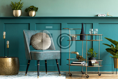 Fototapeta Interior design of luxury living room with stylish armchair, gold liquor cabinet, a lot of plants and elegant personal accessories. Green wall panelling with shelf. Modern home decor. Template.
