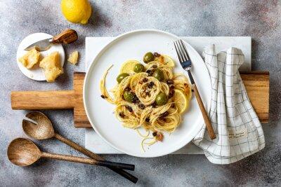 Fototapeta Italian pasta cacio e pepe, spaghetti mixed with grated cheese, green olives, lemon and raisins