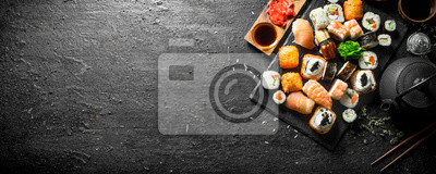 Fototapeta Japanese sushi rolls with salmon, avocado and shrimp.