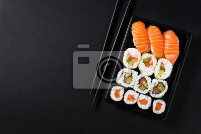 Fototapeta Japoński jedzenie: maki i nigiri suszi ustawiający na czarnym tle. Kompozycja od góry do dołu. Copyspace