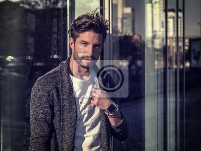 Fototapeta Jeden przystojny młody człowiek w miejskim otoczeniu w europejskim mieście, stojąc
